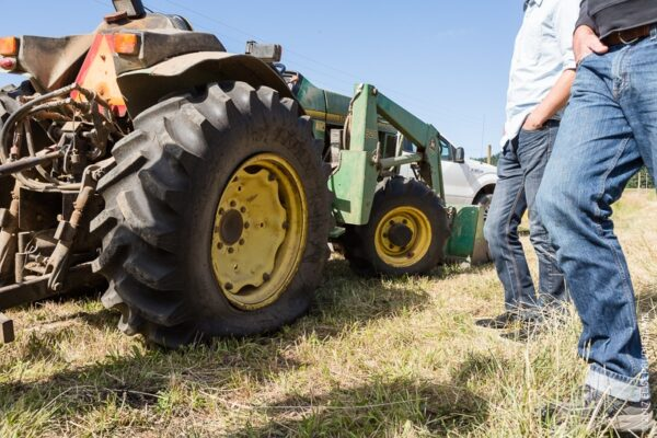 Haymaking team evaluating the flat tire on the John Deere at Three Feathers Estate & Vineyard.