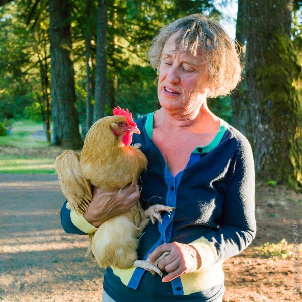 Christine Roosevelt Stimac holding an Araucana chicken on her fa