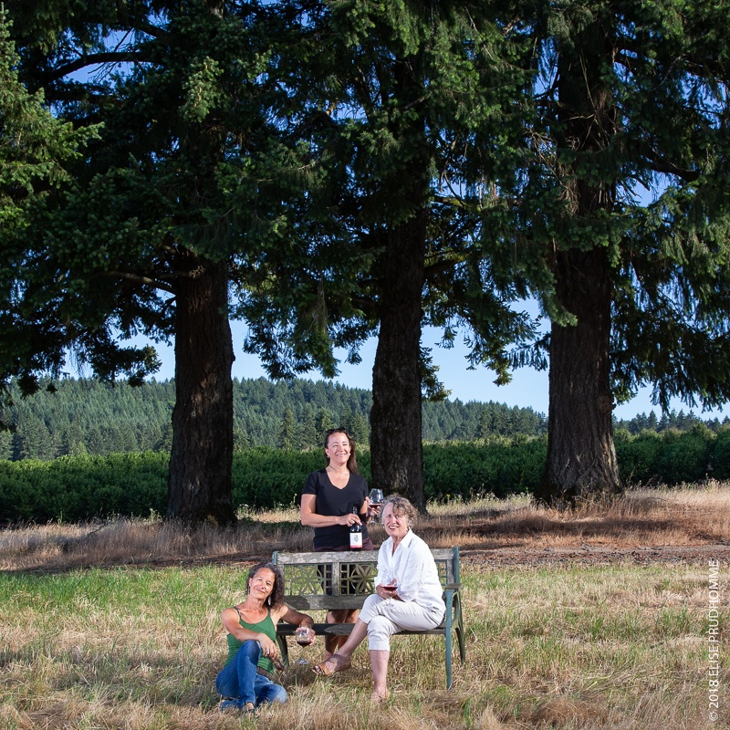 Three Feathers owners pose in front of three douglas fir trees.